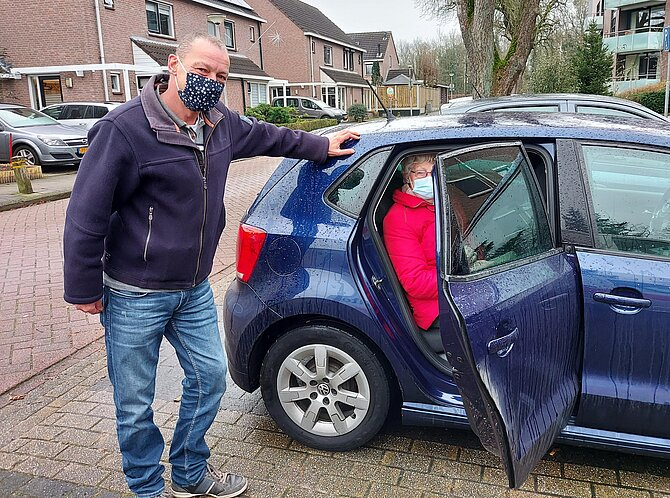 Foto van man met mondkapje bij auto met openstaande deur en vrouw als passagier