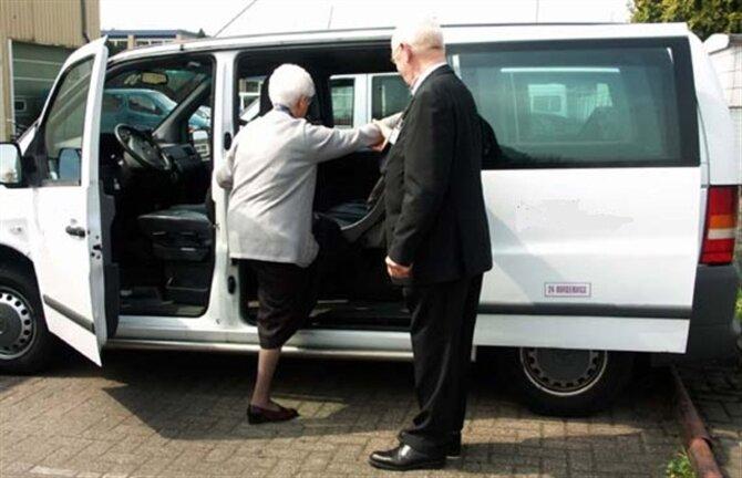 Foto van een vrouw die in een taxibus stapt met hulp van de chauffeur