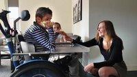 Foto van jongen in rolstoel met liefdevolle aandacht van opppas