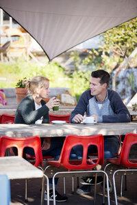 Foto van jonge vrouw en man in gesprek aan een tuintafel