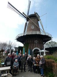 Foto van ouderen bij een oude molen